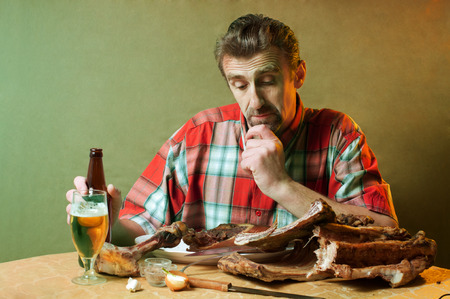 Man with smoked meat of pork and drinking beer photo