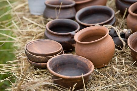 a large number of clay pots lies on a bale of hay