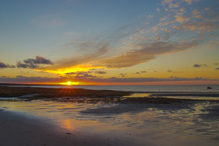 Colorful sunset over Cape Cod Bay and glistening beach Stock Photo