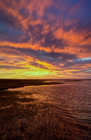 Colorful sunset over Cape Cod Bay and marshy shoreline Stock Photo