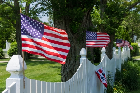 green flag: American Flags on a white fence blowing in the breeze