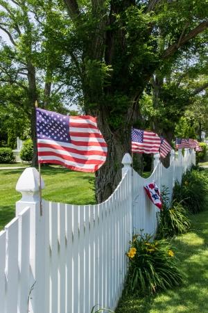 cerca blanca: Banderas americanas en una cerca blanca que sopla en la brisa