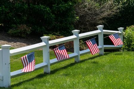 cerca blanca: Banderas de Am�rica colgando de una valla de blanco Foto de archivo