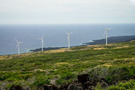 Four windmills on the green slopes of Haleakala on the island of Maui, Hawaii Stock Photo