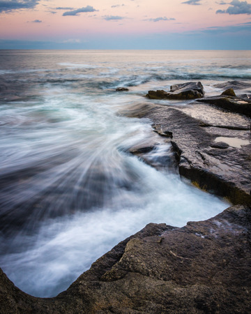 Waves crash at sunset on the rocky coastline of Halibut State Park in Rockport, Massachusetts on Cape Ann, north of Boston. Stock Photo