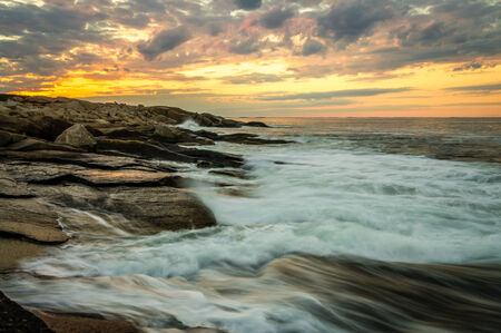 oceanography: Waves crash at sunset on the rocky coastline of Halibut State Park in Rockport, Massachusetts on Cape Ann, north of Boston. Stock Photo