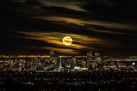 A glowing full moon rises above the skyline of Denver, Colorado, the Mile High City.
