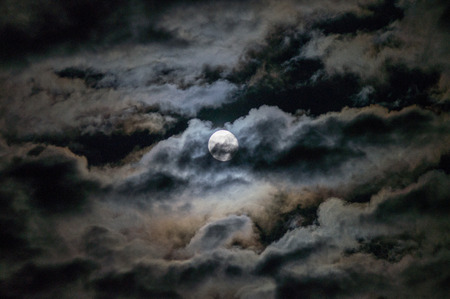The full moon reveals itself amidst swirling clouds on an Autumn night.