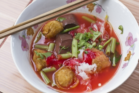 Rice noodles in pink broth with fishballs, squid, fried tofu and kang kung photo