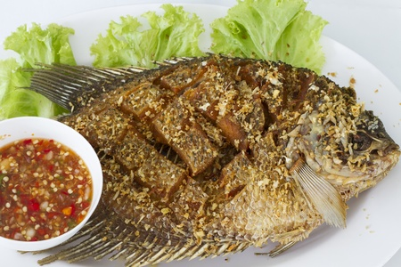 Deep fried red tilapia fish with Thai spicy sauce photo