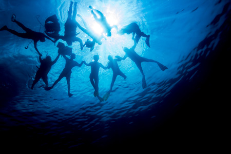 Silhouette of people snorkeling and hold together above the ocean surface