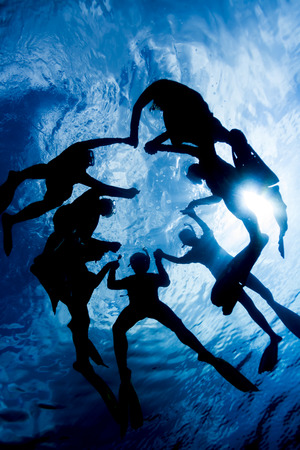 extreme angle: Silhouette of people snorkeling and hold together above the ocean surface