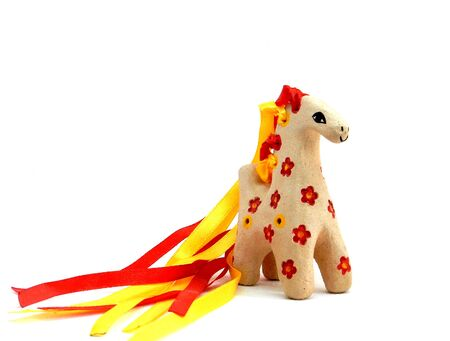 ceramic whistle horse with a mane of yellow and red ribbons and painted with flowers isolated on a white background. High quality photo 写真素材