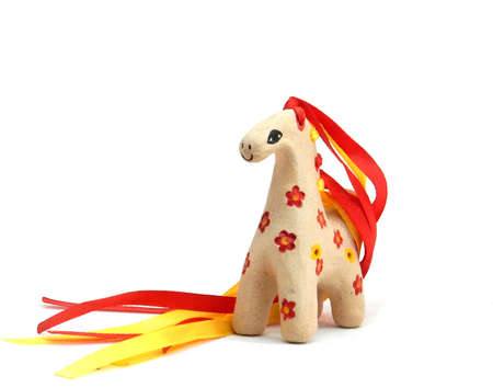 ceramic whistle horse with a mane of yellow and red ribbons and painted with flowers isolated on a white background. High quality photo