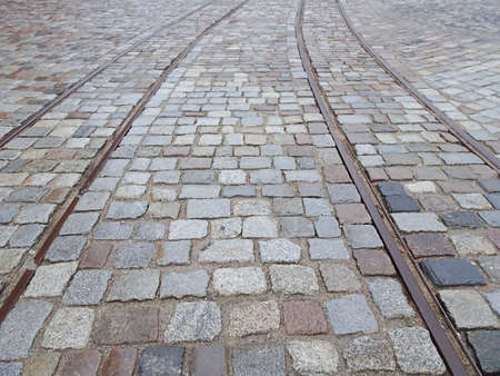 Old tram rails on paving stones converging towards the horizon, selective focus. High quality photo