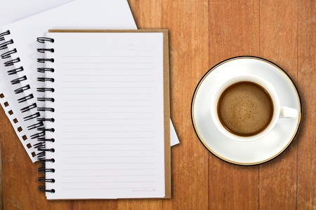 White cup of coffee and notebooks on wood table  photo