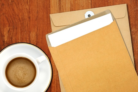 Brown Envelope document and a white coffee cup on a wooden desk  photo