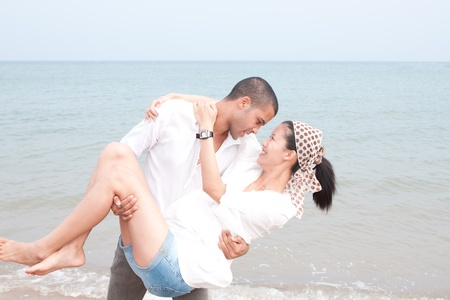 african man and asian woman lover on the beach  photo
