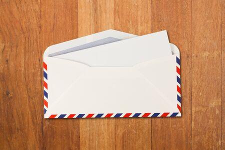 Enveloppe ouverte par courrier aérien et du papier isolé sur le bois Banque d'images