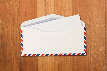letter envelope: open Envelope by air mail and paper isolated on wood