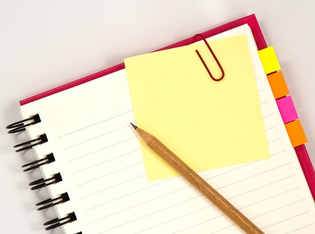 notices: Red notebook with paper and pencil