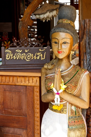 Youre welcome in thai word on wood piece with Thai woman sculpture for Sawasdee welcome of thailand  photo