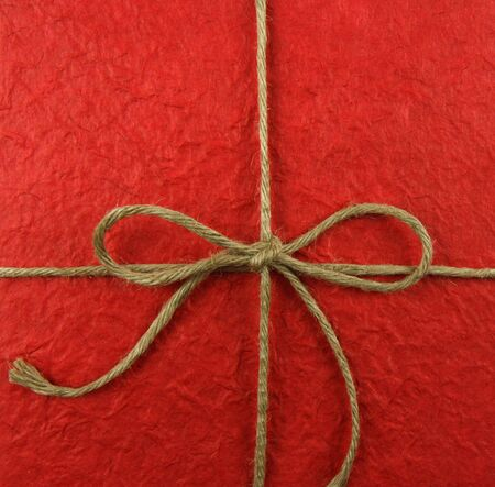 String tied in a bow on red paper photo