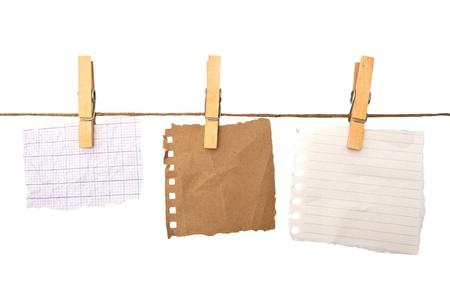 Gros plan d'une note et d'une épingle à linge sur fond blanc