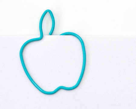 Paper clip in the form of apple on a sheet of paper  photo