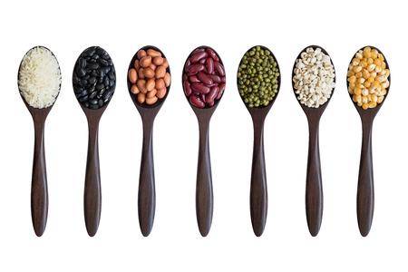 Ensemble de haricots, pois, lentilles, cors, riz sur cuillères en bois isolé sur fond blanc Banque d'images