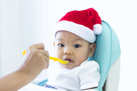 a baby asian in a Santa Claus hat and looking at camera is sitting in a chair and eating  Merry Christmas and Happy New Year holidays.