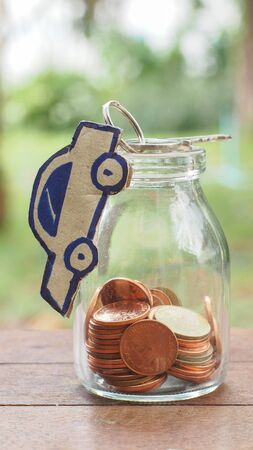 estate: coin in bottle and paper car key on top of bottle Stock Photo