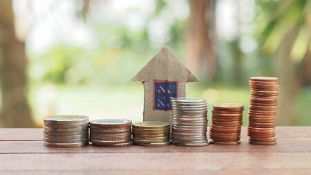 Stack of coin and paper house on the wood table Stock Photo