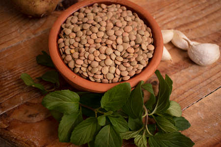Lentils in bowl, fresh mint and garlic on wooden background