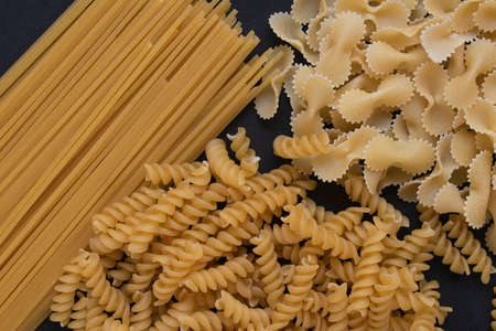 Italian pasta on black background. Farfalle, fusilli and spaghetti. 版權商用圖片