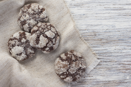 bickie: Chocolate cookies in a linen a napkin on a light wooden background
