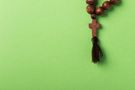 Wooden rosary and cross on green background. Foto de archivo - 106905642