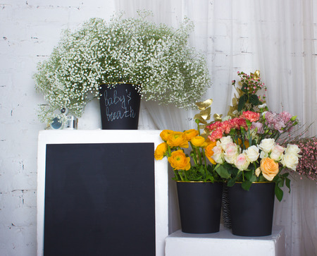 copyspace: Three black buskets with flowers and black desk with copyspace