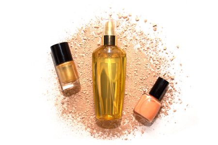 laque: Two nail polishes and hair oil in golden bottle on beige powder isolated Stock Photo