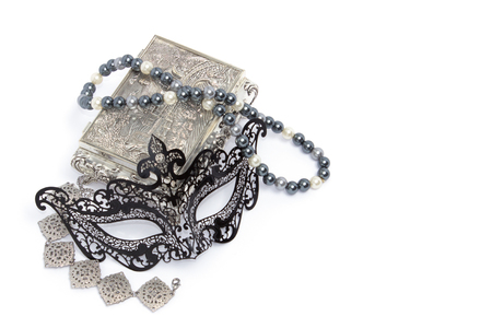 carnivale: Black carnivale mask with silver bracelet and box, and pearl neclace isolated on white background