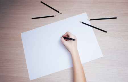 lapiz y papel: Hand with black pencil writing on white paper sheet