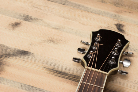 background yellow: Guitar Neck on the old wooden table wall Stock Photo