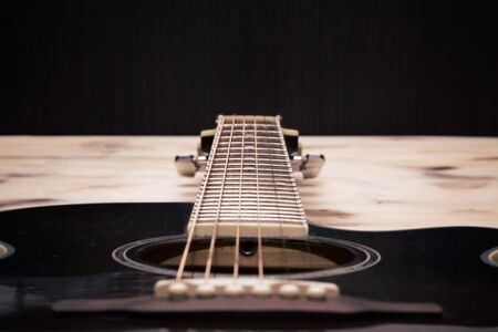 brown background: Guitar Neck on the old wooden table wall Stock Photo