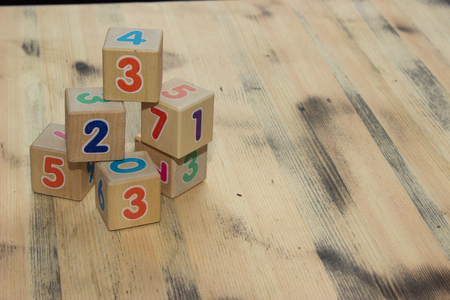 brown background texture: Cubes with colors numbers on old  wooden table background
