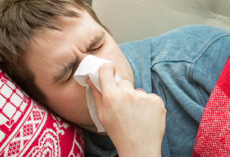 sniffles: Man with cold lying and sneezing in a tissue