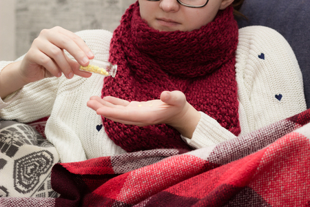 sniffles: sick woman with glasses and red scarf taking pills in bed