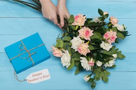 agradecimiento: Tarjeta del d�a de madres con las rosas r�sticos de madera de fondo azul con el regalo Foto de archivo