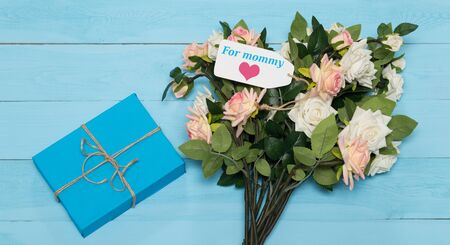 agradecimiento: Tarjeta del día de madres con las rosas rústicos de madera de fondo azul con el regalo Foto de archivo