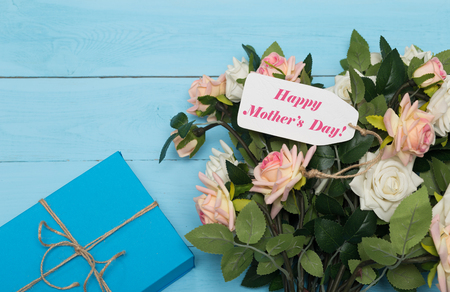 agradecimiento: Mothers day card with rustic roses on blue wooden background with gift