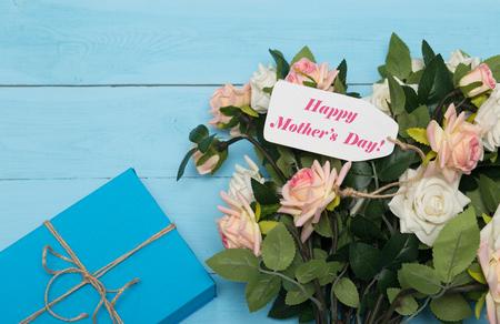 gratefulness: Tarjeta del d�a de madres con las rosas r�sticos de madera de fondo azul con el regalo Foto de archivo